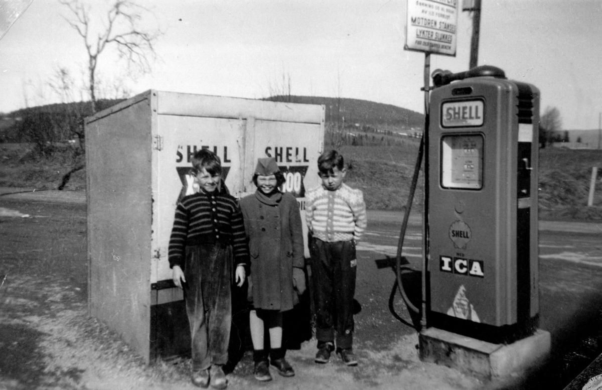 Tre barn ved en bensinpumpe.