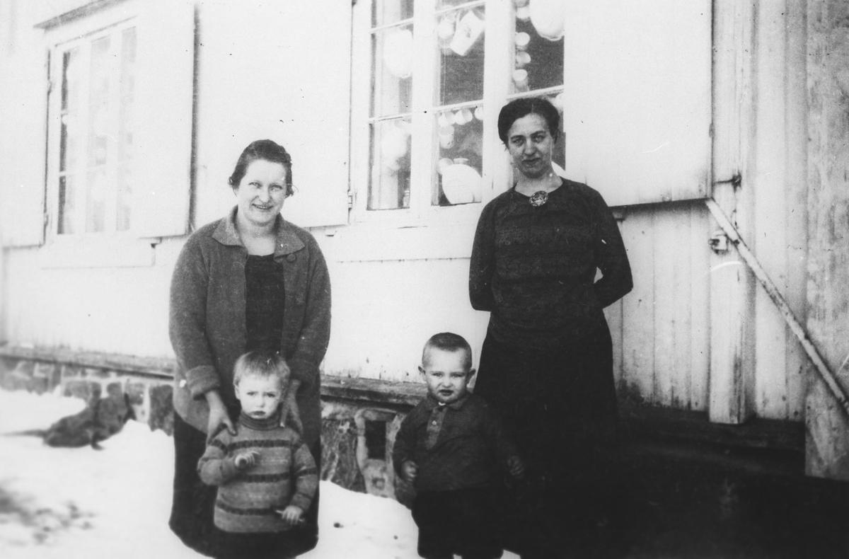 To kvinner med to barn foran den gamle butikken på Nardu Rolstad m/postkontor.