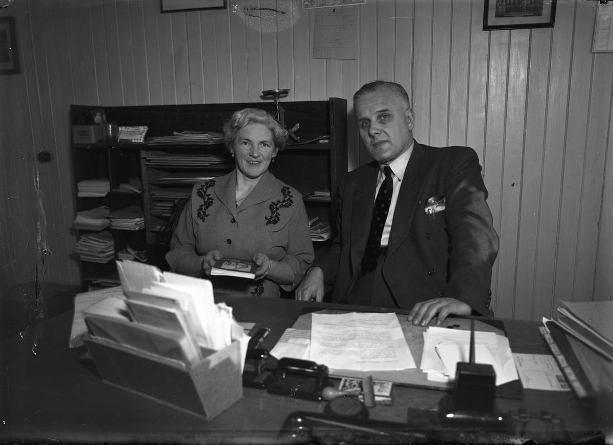 """Toten Folkehøyskole. Fra et kontor. Timeplan med """"Toten Bokhandel"""" henger på veggen. Året er 1956."""
