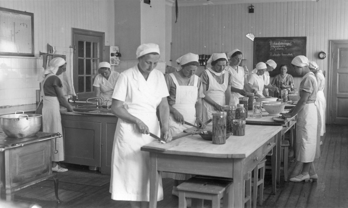 Jenter på et skolekjøkken – Akershus Husmorskole. Rektor Helene Hval uten uniform.