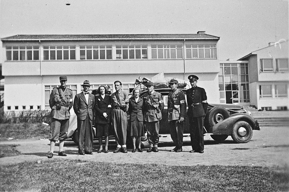En del av avsnittsledelsen H.V. og andre. Ved Romerike folkehøyskolee, Jessheim. 1945. Fra v.: Alf Røvang, Odmund Eid, Einar Brønlund, Sigrid Brønlund, Bertel Bøhnsmoen, Marte Fagernes Nerdrum, lensmannsfullmektig Martin Tandstad og lensmann Jacob Reed.