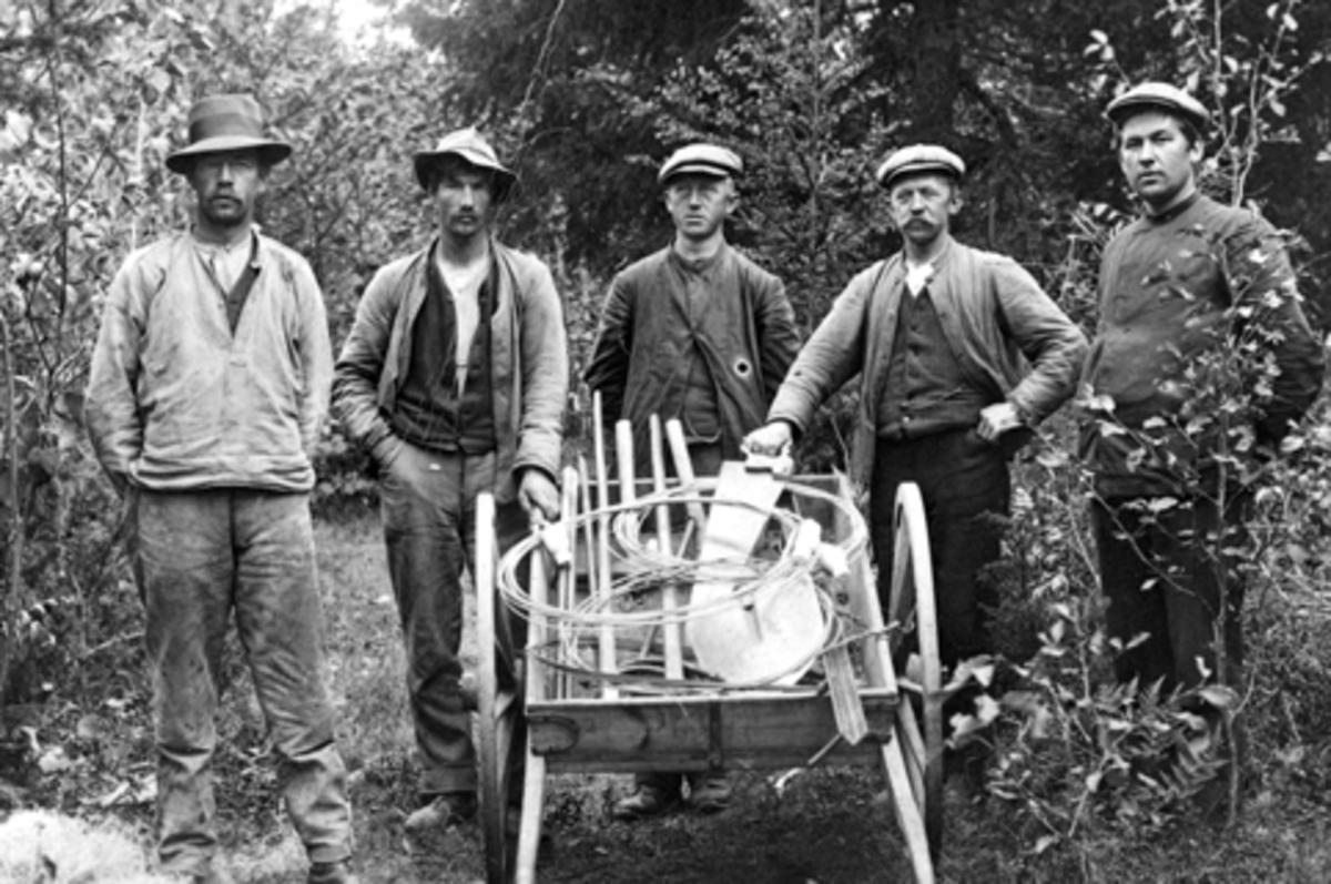5 telefonmontører på jobb. Fra venstre er Lars Norengen, Johan Olsen, Aksel Knutsen, Kristian Olsen, Lars Haugli. Håndkjerre med utstyr. Ringsaker.
