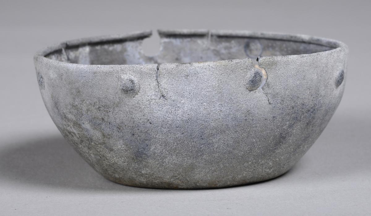 Skål i metall. Enkel og ganske smal i formen. Det er slått inn et enkelt mønster bestående av sirkler langs kanten.
