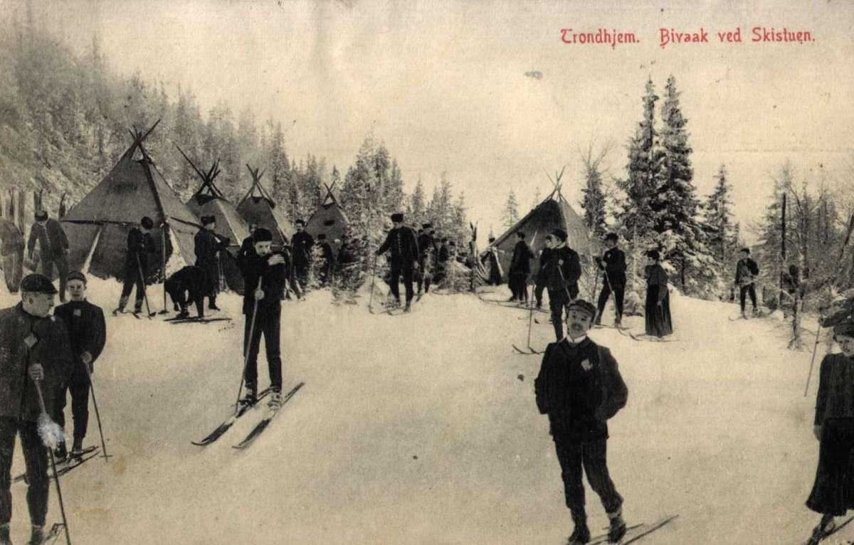 Postkort. Jule- og nyttårshilsen. Foto. Svart/hvitt. Vintermotiv. Bivuakk ved Skistua i Trondheim. Skiløpere. Stemplet 24.12.1907.
