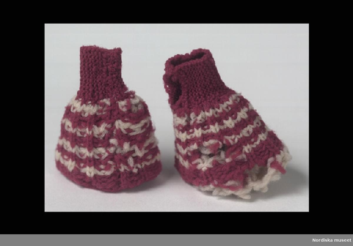 Inventering Sesam 1996-1999: L 6 cm Dockmudd stickad av ullgarn, randig i vitt och lila. Hör till docka 202.174. Leif Wallin jan 1997