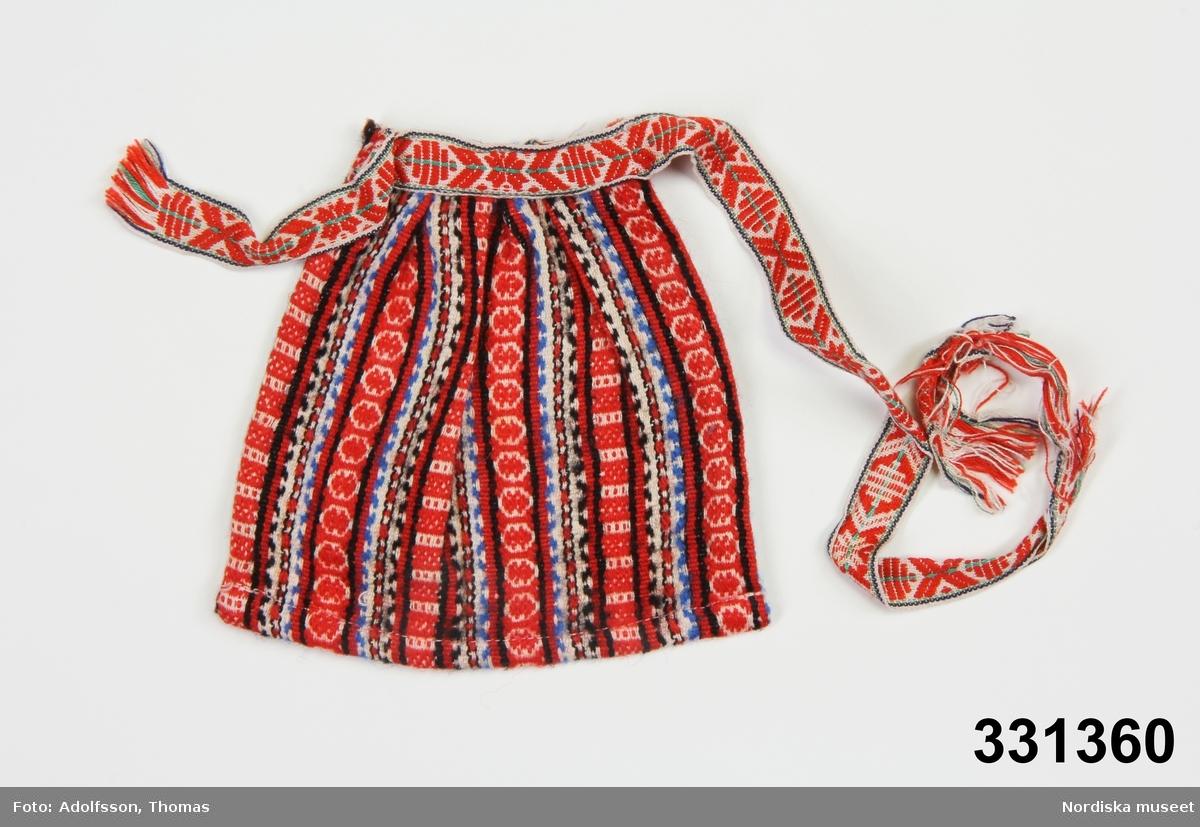 Föremålet ingår i en större samling dockkläder NM.0331348-NM.0331482 (ej NM.0331362).Mönstrat, vävt förkläde för docka.  Hör till orange dockklänning (NM.0331359).  ./Karin Dern 2011-09-13