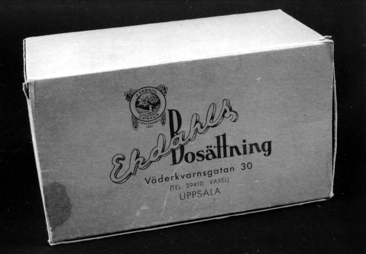Kartong av gråblå blekt papp, hopfogad med metallklamrar, fällock med firmamärke och text i blått: Ekdahls Bosättning, Väderkvarnsgatan 30, Uppsala.