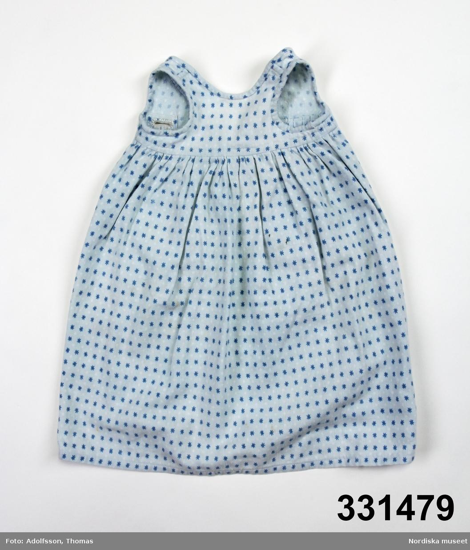 Ljusblå nattröja för docka med mönster av blå stjärnor och vita prickar. Ärmlös, bomullsband för knytning bak, öppen baktill.  /Karin Dern 2011-09-13