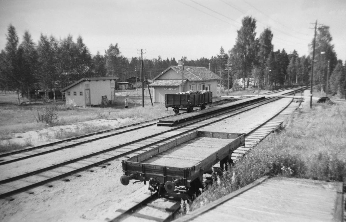 """Åpne godsvogner på Kløftefoss stasjon. I Spor 1 står en L4 type 1, som ble anskaffet i 1916-17 fra Tyskland. De var av standardtypen """"Halle"""". Norsk Hovedjernbane stod for kontakten og det ble innkjøpt hele 646 slike vogner, hvorav Rjukanbanen kjøpte 50. Resten ble fordelt på NHJ og NSB. En slik vogn er bevart. I spor 3, nærmest, står en grusvogn type  M1."""