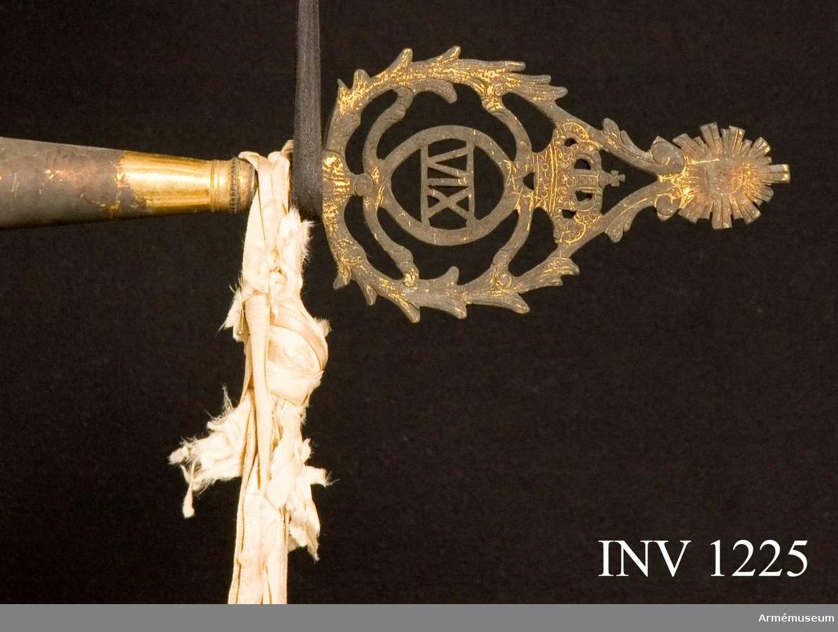 """Grupp B.  På det gulvita kyprade fansidenet sitter i mitten ett broderat monogram föreställande två motställda """"C"""" inneslutande """"XIV"""". Broderiet utfört i plattsöm med silke och silvertråd. Ovanför monogrammet sitter en kunglig krona utförd i plattsöm med foder i rött silke. I fanans hörn sitter snedställda kronor i rosa silke, d v s bleknat. Fanspetsen har Karl XIV Johans monogram, dock mycket ärgat. Fanstången är gulvitmålad. Kravatten, den lilla del som återstår, är uppsydd på ett bomullsband. Fodral hör till fanan.   Samhörande nr är 25394:1, 25394:2, 1224-1228."""