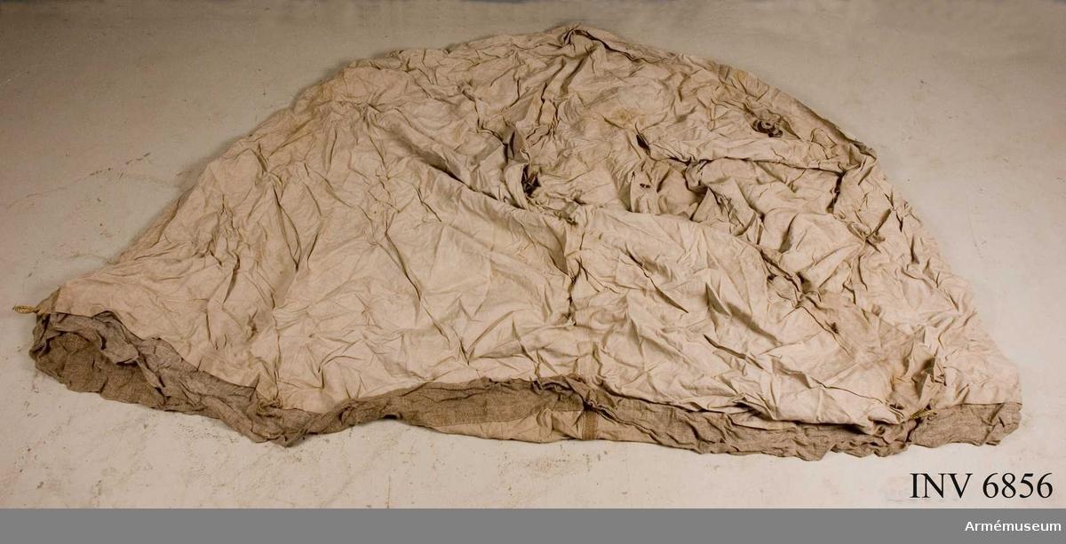 Sth 230O mm (i mitten av tältet), h t hörn 1860 mm (kappan medräknad), omkr 8000 mm. Tältet utgöres av en enda del. Fyra  väggar och fyra triangelformade takdelar. Tak/väggdelar är hopsydda med varandra för hand. Insidans sömmar är förstärkta med 40 mm bred och glest vävt sadelgjordsband. I taksömmen som  förbinder vägg/tak är svarvade knappar fästade i sadelgjordsbandet, förmodligen avsedda att hänga kläder i. Dörröppningen är en enkelt slits. Ovanför denna finns ett hjärtformat lädermärke. Dörren kan vikas upp och fästas med Ögelknäppning åt vardera sidan. Dessutom finns numera ditsydda vanliga benknappar, vilka man knäpper på insidan. Varje hörn är läderskott och försett med en rund järnring som är avsedd för att fästa tågvirkena i vid uppsättningen. Längst ner löper en s k kappa. Ovanför denna är tampar fästade i tältduken vari tältet förankras i marken med tältpinnar.  Samhörande nr är 6852-6857.Tält.