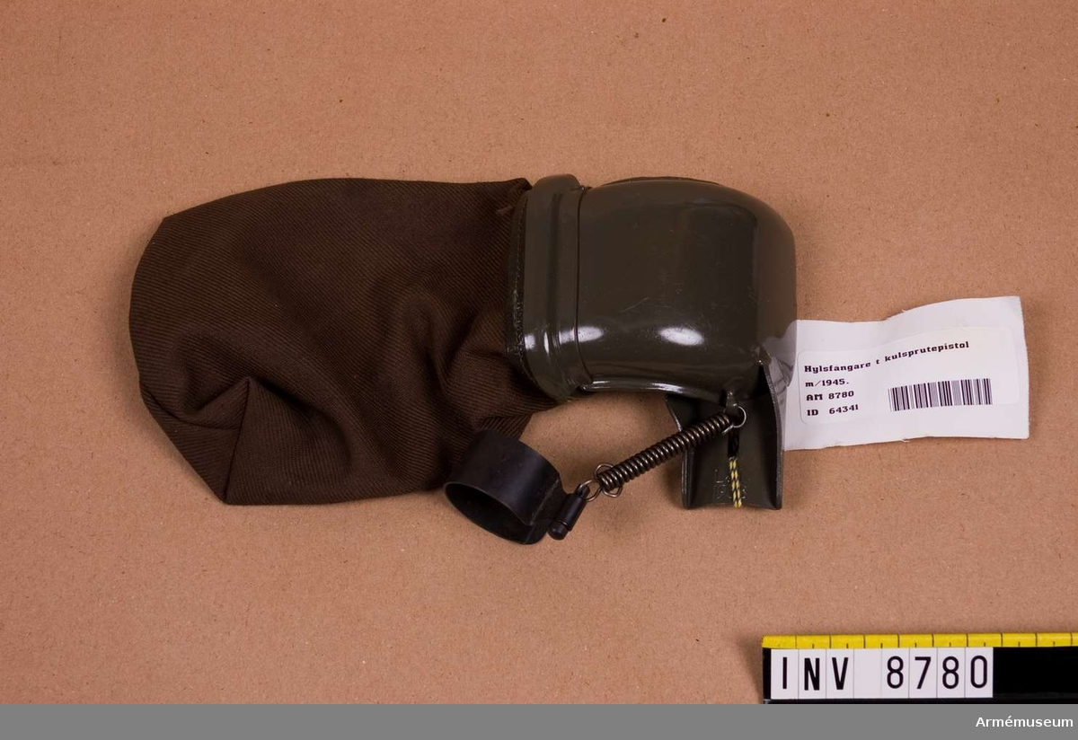 Hylsfångare till kulsprutepistol m/1945.Märkt L & L 1958.Höjd med påse 230 mm.Hylsfångare består av: hylsavledare, klämring, fästklack och hylspåse av väv. Se Soldatinstruktion för armén Materiel 1969. sid 56-57.