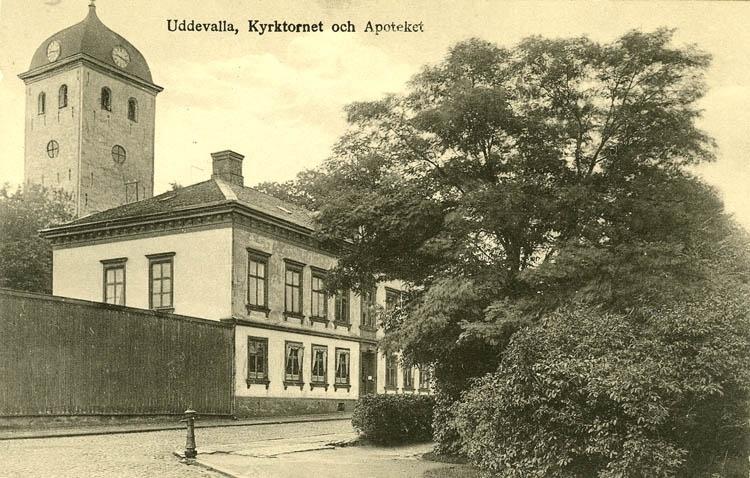 """Tryckt text på bilden: """"Uddevalla kyrktorn och Apoteket.""""    """"Förlag: Rosa Nilsson Pappershandel, Uddevalla."""""""