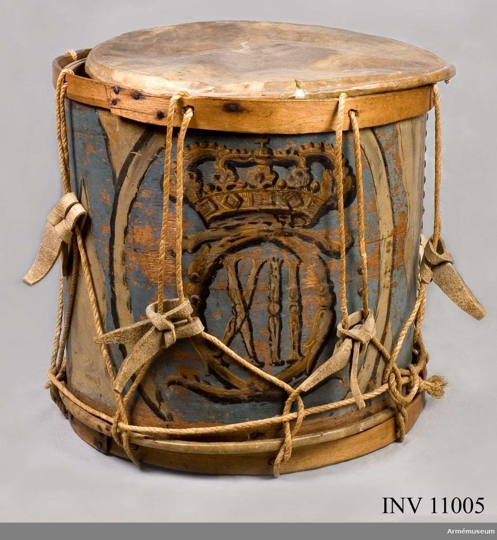 Grupp B III.  Gjord av trä, omlottböjd vid ändarna, som är spikade (nitade) på varandra i två rader. Ramar av omålat trä (gula), också spikade omlott vid ändarna. Snörad. Målad i ljusblåa och beigegråa flammönster med Karl XII:s namnchiiffer, krönta, i guld och svart färg i ett ovalt fält. Ett runt hål finns mitt på trumvägen och där nedanför en pånitad, avlång järnplåt. Skinnen defekta. Färgen delvis borta.