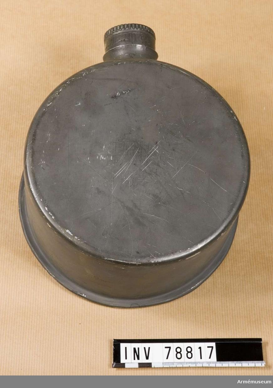 Grupp I.III. Rund. Av bleckplåt med öppning och kork (med järnbeslag). På baksidan en ring med karbinhake för att koppla flaskan till utrustningen.