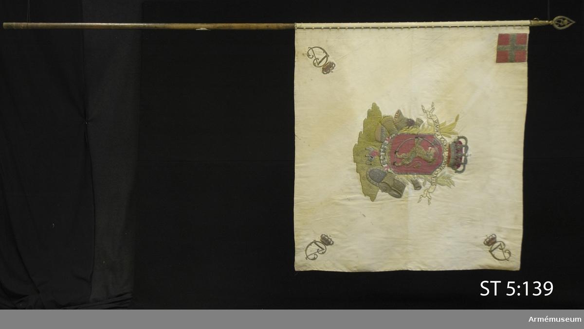 Dubbel duk av vit sidenrips ihopfogad av två våder à 58 cm. Tungt broderi av guld, silver och silke, paljetter och någon applikation delvis i relief.  Motivet består av norska riksvapnet. Skölden är omgiven av lager- och palmkvistar, elefantordens kedja och trofégrupper samt vilar på en grön kulle. Över skölden en sluten krona och ett språkband med texten: SEMPER EADEM FIDUCIA GENTIS. I det övre hörnet på stångsidan är den danska flaggan, dannebrogen, utförd i läggsöm i silver och rött silke. I de övriga hörnen den dansk-norske kungen Christian VII:s monogram, C7, under sluten krona. Motivet är lika på båda sidor. Duken är virad runt stången och fäst med tre rader förgyllda tännlikor. De är spikade med 3 cm mellanrum genom ett 1 cm brett guldband. De tre översta tännlikorna närmast holken har bokstäverna SF (Söndenfjeldske) ingraverade. Stången är rund och omålad, nedtill försedd med en doppsko av mässing. Spets av förgylld mässing. Bladet är genombrutet med Christian VIIs monogram under krona. Bladet är gängat mot en konisk holk som har en ögla för banderollen.