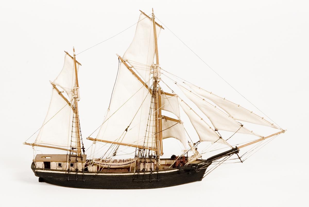 Modell av galeas i block med segel av bomull. Kabyss vitmålad, storbåt midskepps. Kajuta med brunt tak. Svartmålat skrov.Föremålets form: Vattenlinjemodell