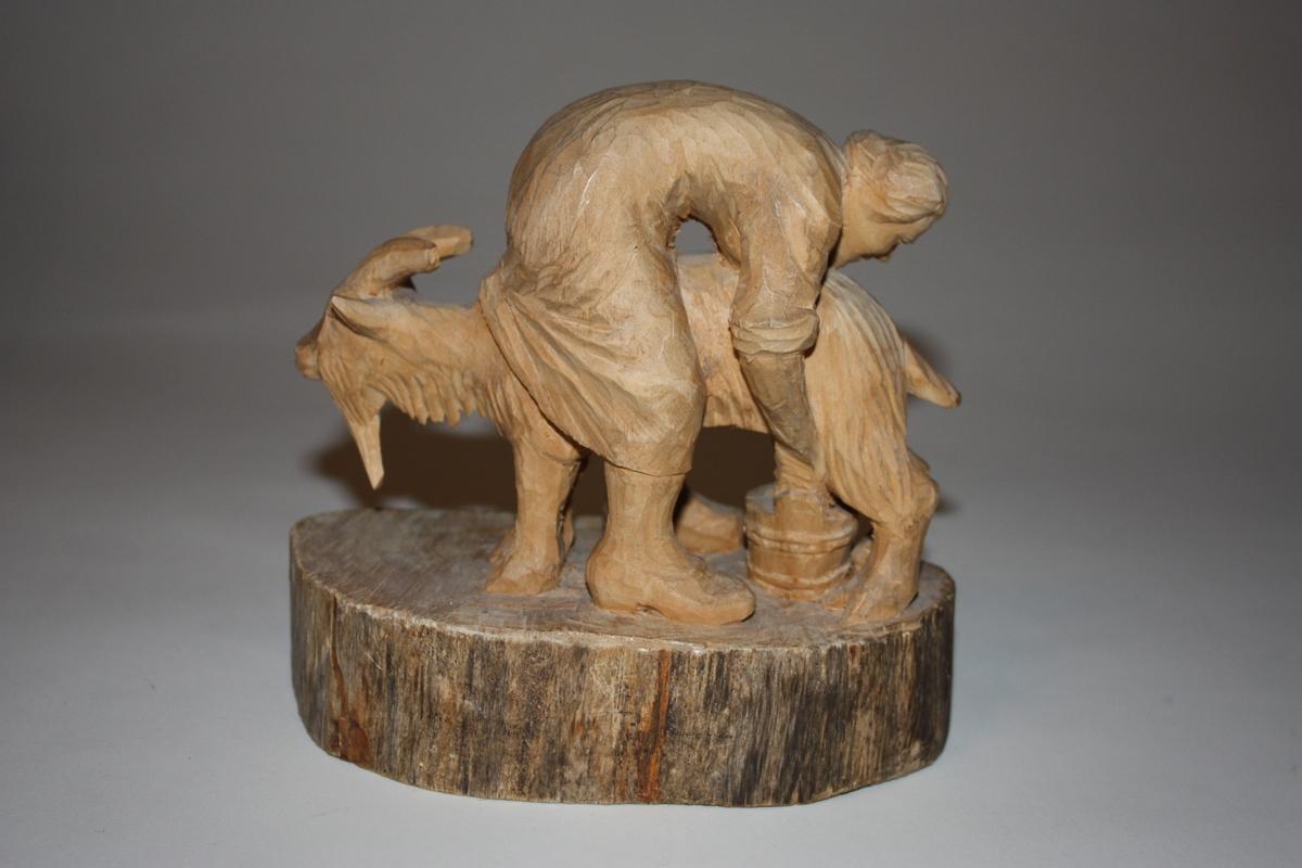 Trefiguren syner ei kvinne som står bøygd over ei geit og mjølkar. Figuren er heilskoren på fast sokkel.