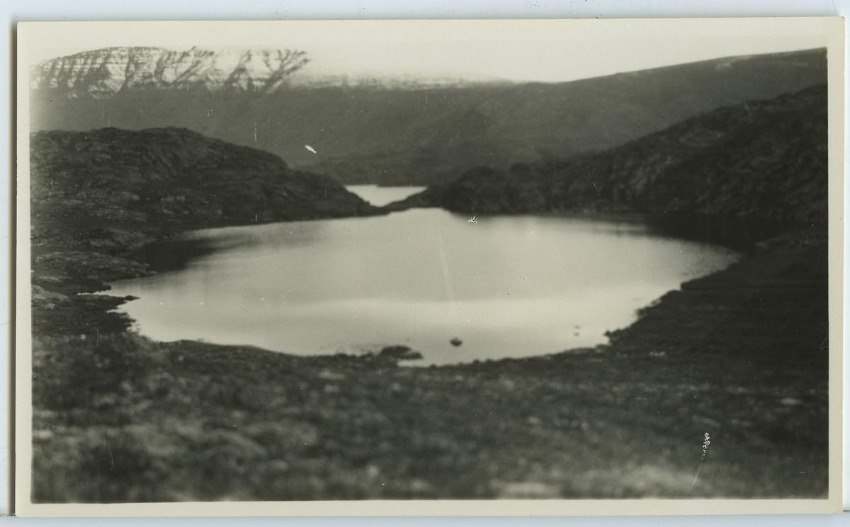 'Sjö och berg. En av tre sjöar som binder samman Kasorsuak halvön med resten av Diskoön. Tre sjöarna heter Mellemsoe (Mittensjön), Lillesoe samt Lang-soen (Långsjön). Se även fotonr. 5217:88 och 89. ::  :: Ingår i serie Fotonr. 5217:1-103. Se även hela fotonr. 5202-5218 med bilder från Frits Johansen.'