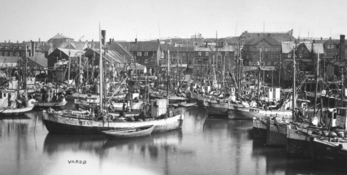 """Bildet er tatt i 1932 og viser båter på havna i Vardø.  Den ene båten heter """"Florida"""" av Skallelv og var eid av Harjobrødrene. I """"Fortellinger fra Vardø"""" kan man lese en artikkel om da båten ble bygget. To registreringsnumre sees - F 29 N.V. og T 5 N. Bildet illustrer godt hvor mange båter som kunne ligge inne på havna i Vardø."""