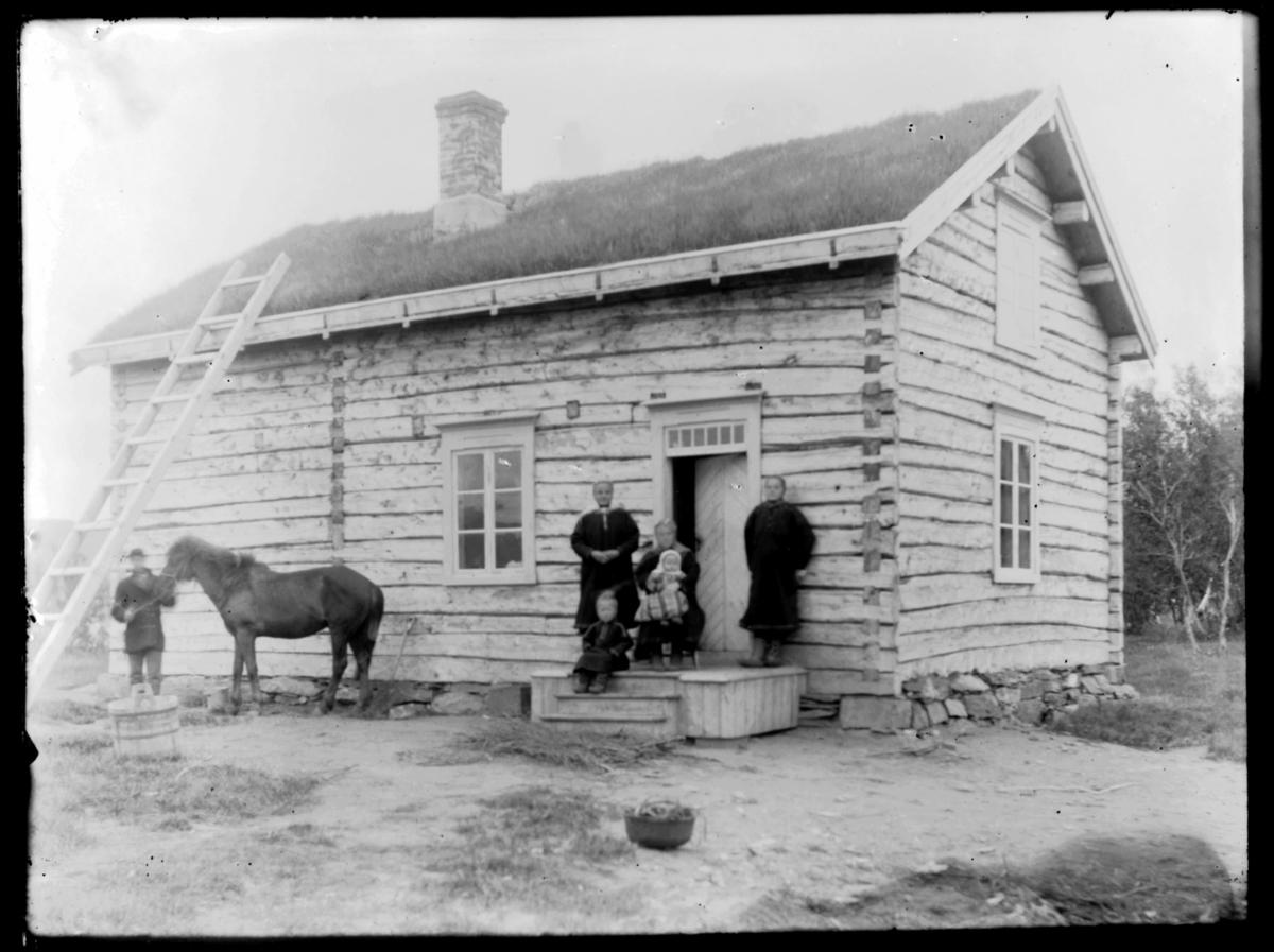 Familie på trappa til et tømmerhus