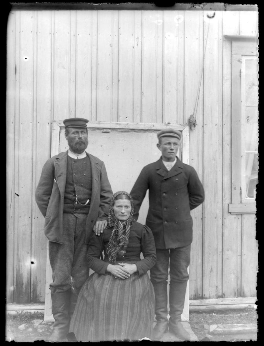 To menn og en sittende kvinne fotografert foran et pakkhus