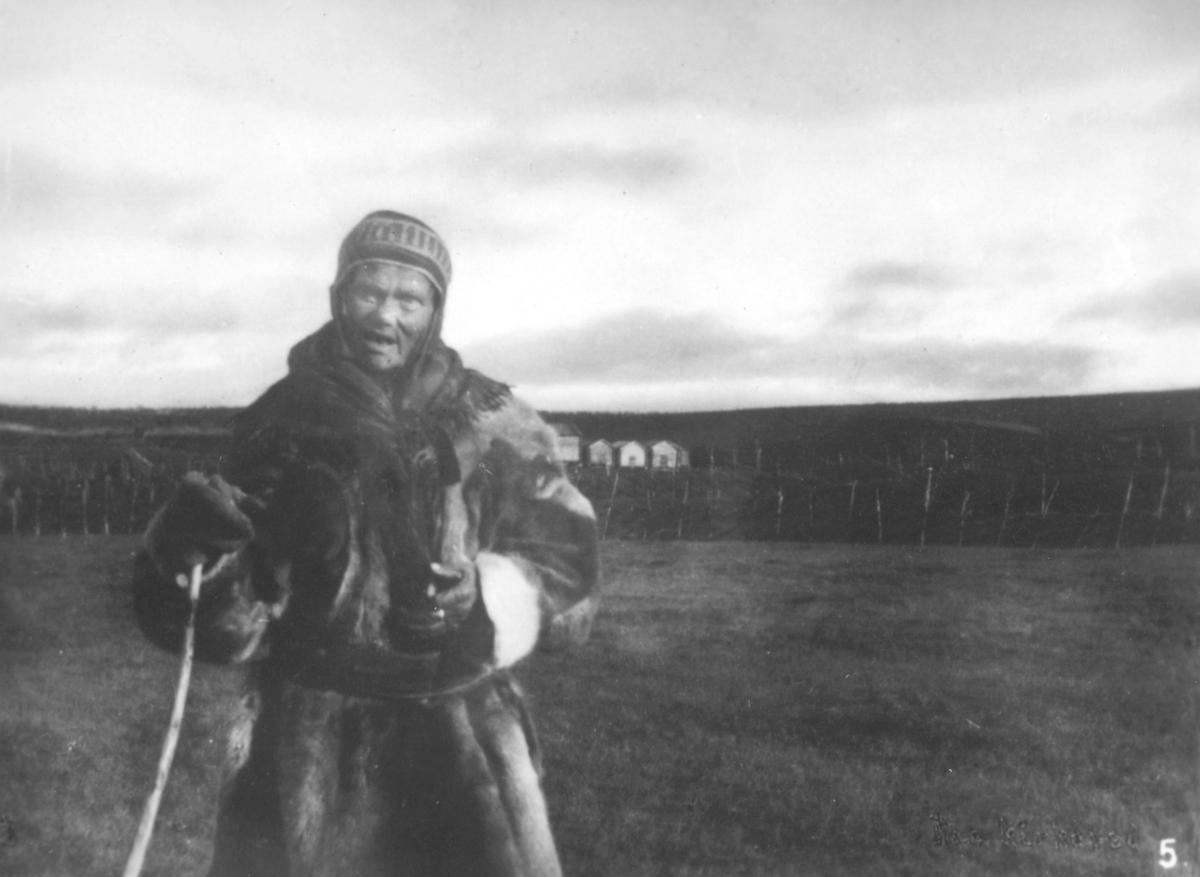 Bilde nr. 5 i serien '10 amatørbilleder fra lappernes hjem og liv i Finnmark', se FB 93164-001. 'Lappekone, i Kautokeino paa vei til kirke.'  Kvinnen er kledt i pesk, lue, votter og skjerf. I handa har hun en kjepp. Det er ikke snø.