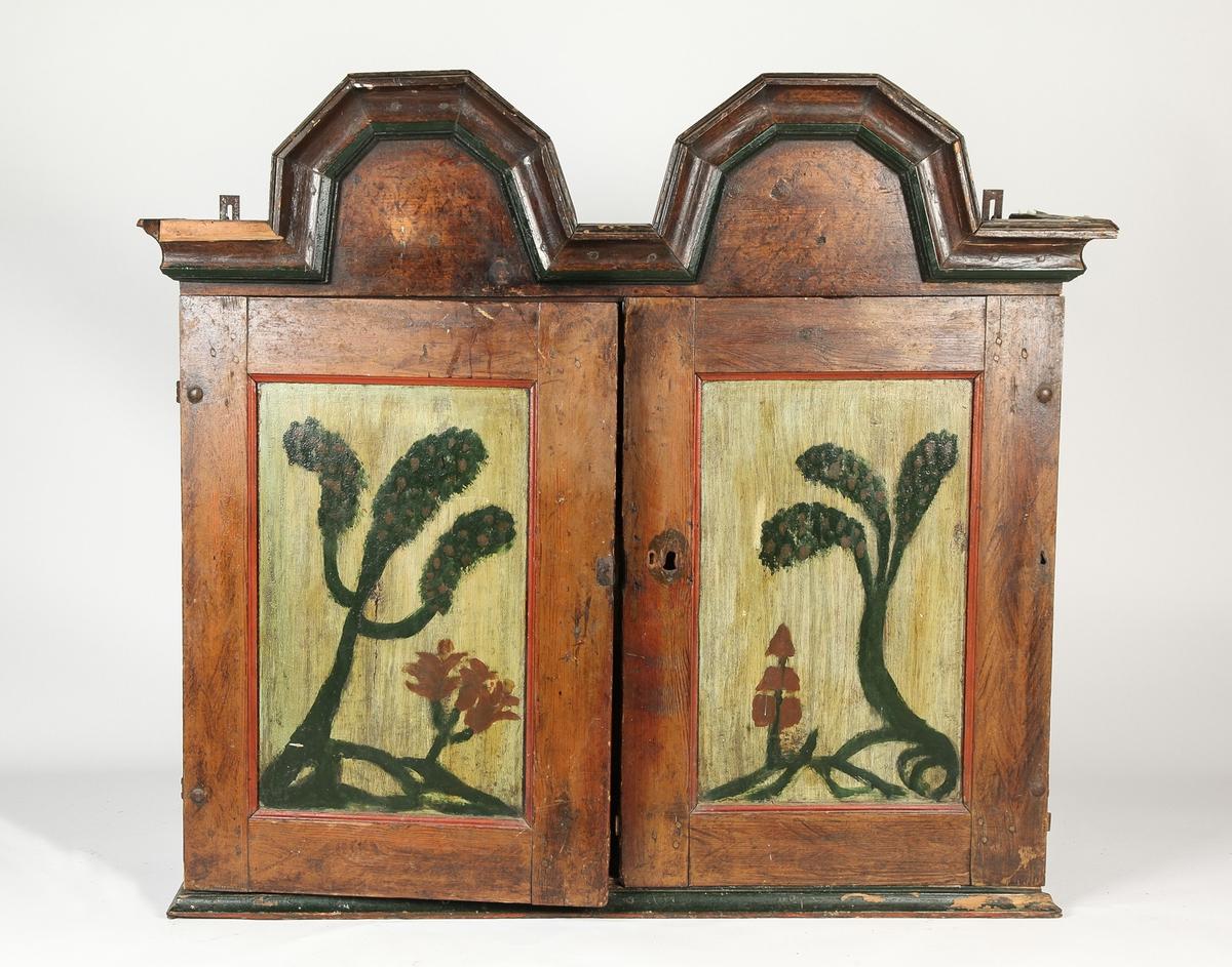 Bygdesnekret hengeskap med to dører og gesisms med to høye buer. Enkel blomsterdekor på dørene. Tre skuffer. Grov utførelse og dekor. a. skap b-d. skuffer