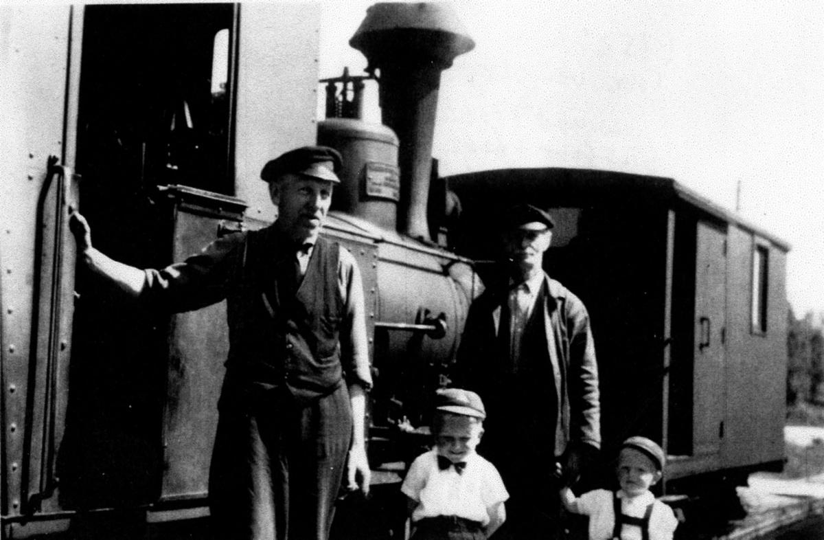 Lokomotivpersonale med barn foran Lillesand-Flaksvandbanens damplokomotiv nr. 2.  Bildet er tatt i forbindelse med nest siste tur på banen før nedleggelsen 15.6.1953.  Fra venstre Tønnes Have, Gunnar Flakk, Gustav Flakk (bestefar), Einar Flakk