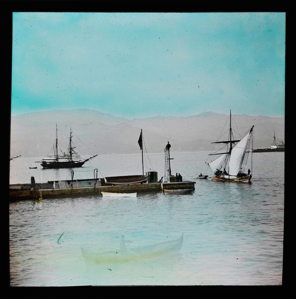 """""""Smyrna."""" (Bildetekst fra album) En kai/brygge. Mange seilbåter ute på vannet. Håndkolorert utsnitt."""