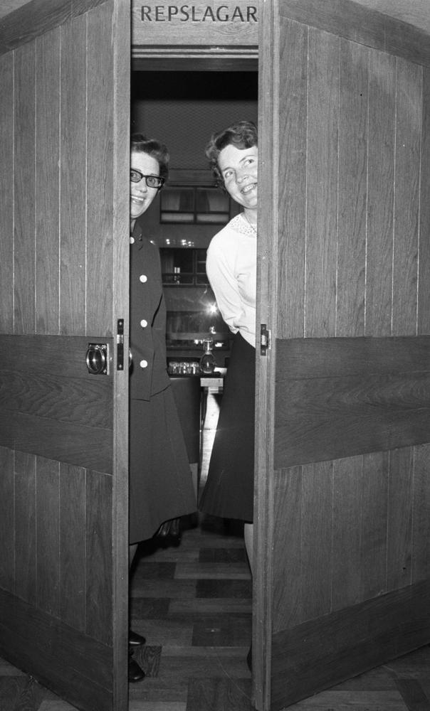 """Lo- Handels 17 oktober 1966Två kvinnor står i en dörröppning med dörren halvöppen och ler. Den ena bär mörk kavaj med vita knappar, mörk kjol, mörka skor samt glasögon. Den andra bär ljus blus, mörk kjol och mörka skor. Rummet bakom dörren skymtar i bakgrunden. Ovanför dörren syns texten """"Repslagaren."""""""