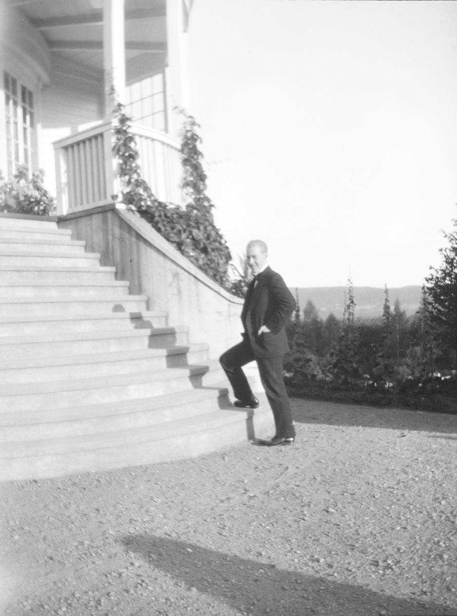 Iacob Ihlen Mathiesen står på nederste trinn i verandatrappen fra den viktorianske hagen opp til hovedhuset på Linderud Gård.