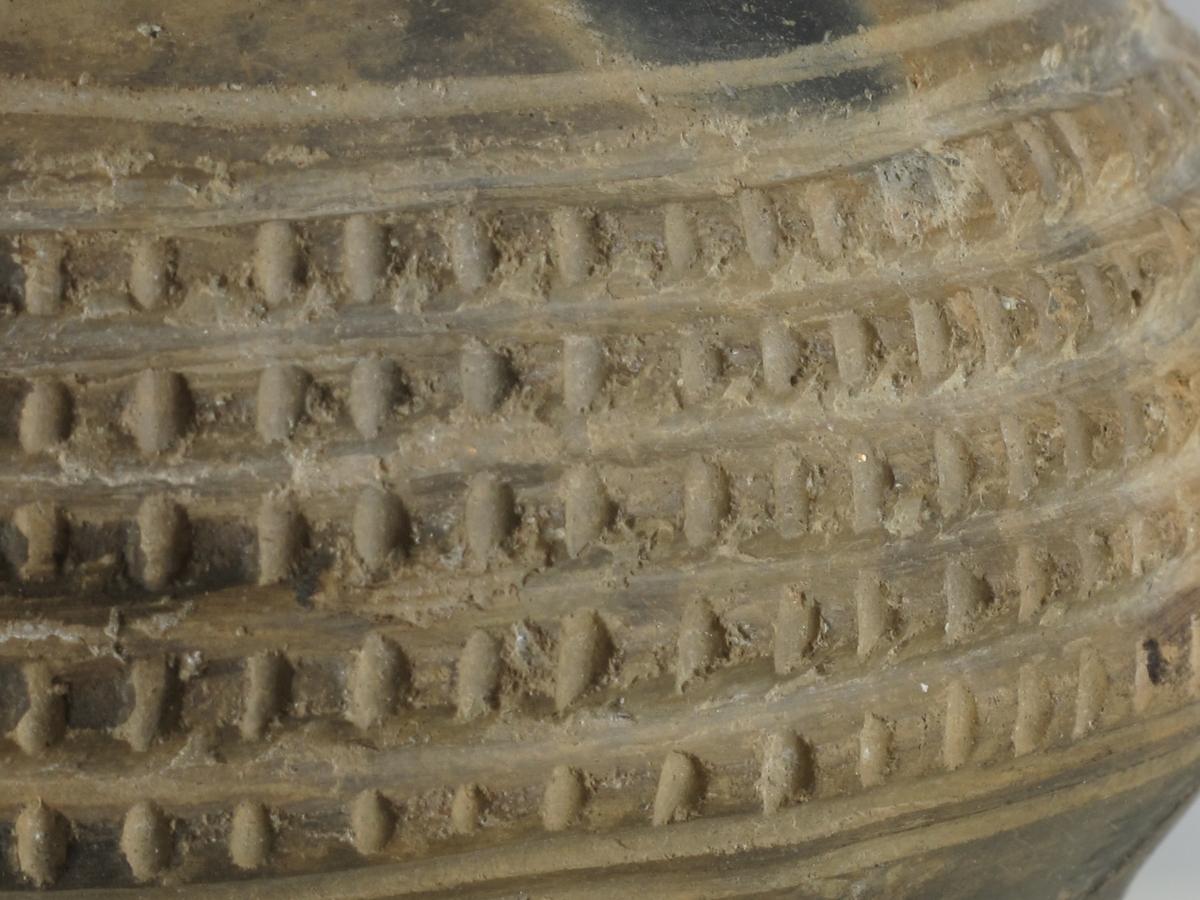 """""""Vorte""""beger avbildet Bøe: Keramikk, fig. 137, omtalt s. 100 og s. 105. Det hesteskoformete mønster som finnes på skulderen, omgir også bunnen, som er noe oppdrevet. En del restaurert."""