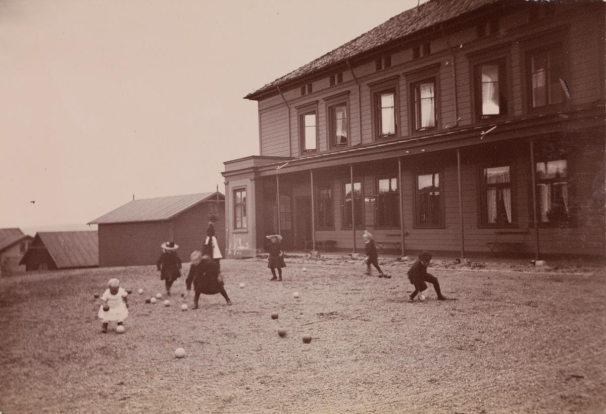 Christensen-barna spiller Boccia foran Linderud Gård hovedhus. I bakgrunnen ei kvinne.