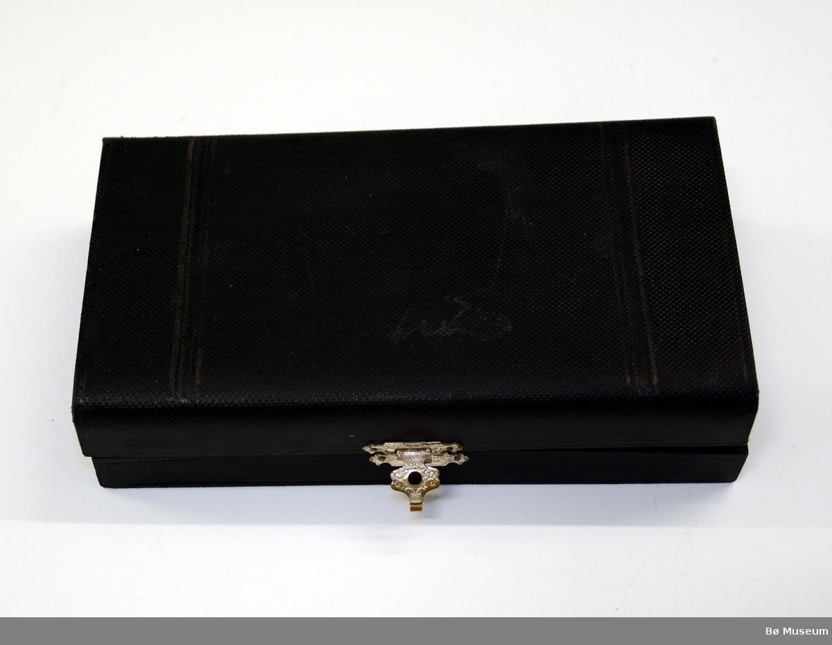 """Liten sølvskje, dessertskje - 1 av 6 - i etui. I etuiets lokk er det festet en lapp med 2 sikkerhetsnåler. Tekst: """"Hans Kleppen - Springlauf ....... 2 Preis(?)"""". Kan være fra Klosters i Sveits i 1928 - der kom han på 2. plass.  Stempel: (hus) WELLNER (90) - 21 Mønster: """"Mozart"""""""