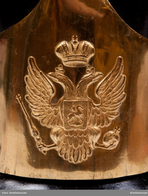 Grupp C I.   Hjälm av lackerat svart läder med tagelliggare försedd med mässingsvapenplåt. På vapenplåten ryska dubbelörnen. På framsidan en skärm av läder med mässingsbeslag. Foder av grov linnelärft.