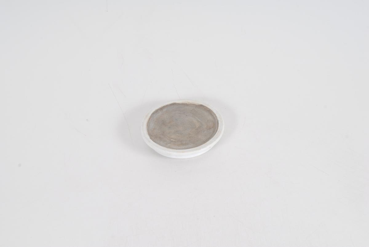 Form: rund og flat, uten håndtak Tilstand: dersom ikke gjenstanden mangler en del er den hel med noen små hakk og merker. Men oppå lokket er det en liten forsenkning med en grå masse som kan ha vært en slags sement til å lime noe annet fast med. I så fall er gjenstanden ikke komplett. Uansett mangler den krukken sin.