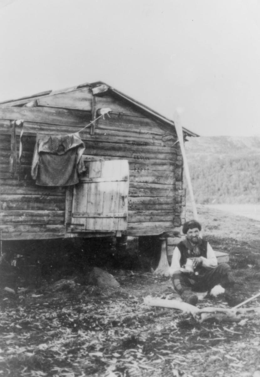 En skoltesame fra Neiden. Han sitter utenfor en gamme med en boks i hendene. På gammeveggen henger en busserull/genser på en snor. Samen har på seg skjorte og vest.