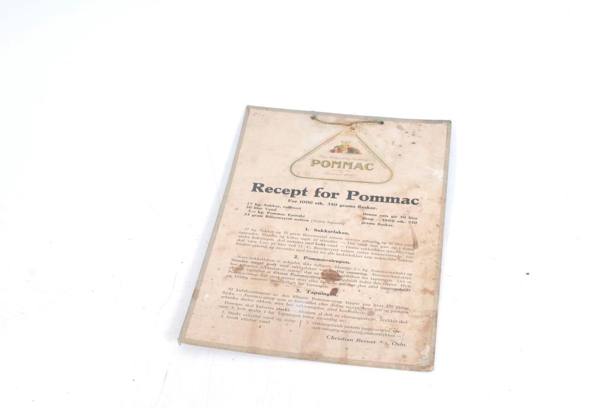 """skrift, pålimt etikett til varen """"Pommac"""", med stilleben av frukt og et stettglass"""