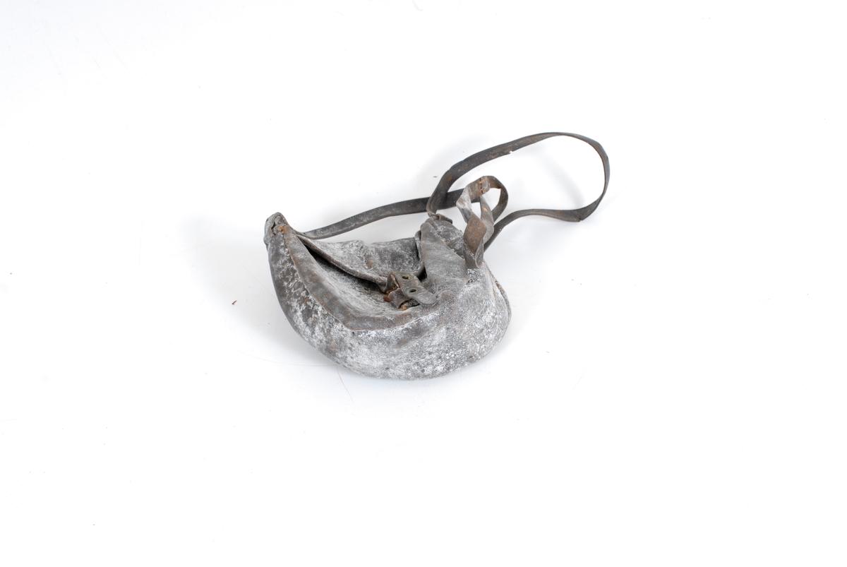 Form: Liten, m. lukkespenne, frontstk.,bunn/sidestk. Remstk. m. 3 hull festet på u.side av lokk. Spenne midt på fremstk. Remmen festet øverst på bunn,