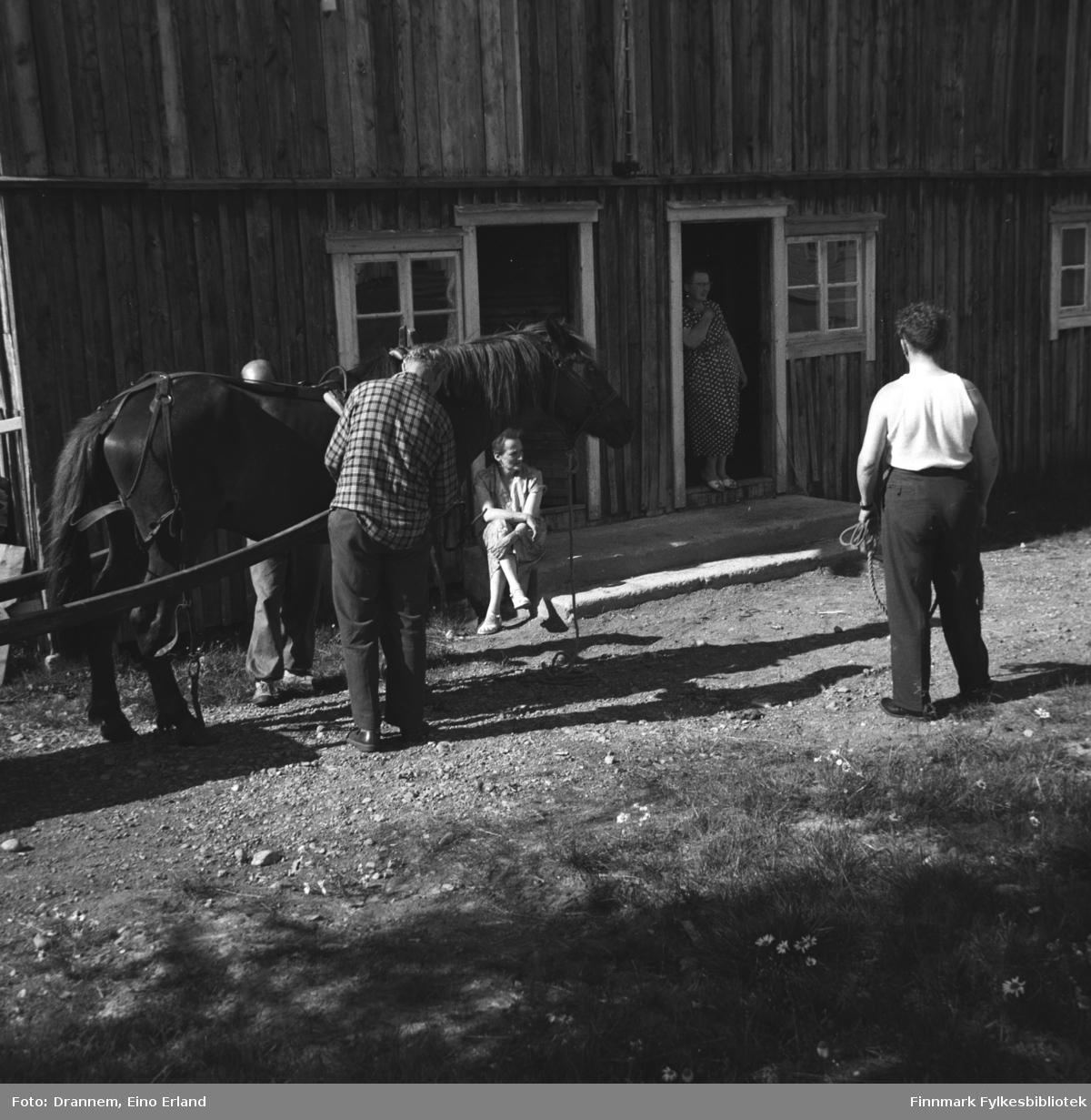 Fem personer og en hest  fotografert utenfor en stor driftsbygning.