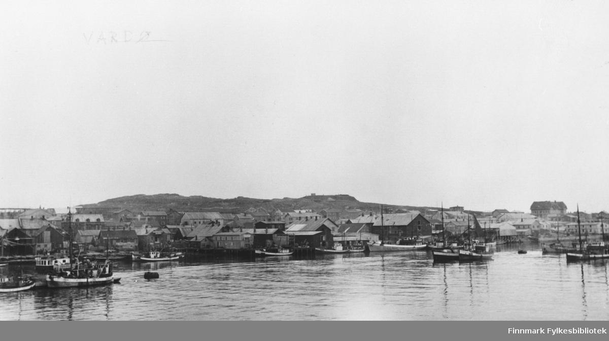 Havna i Vardø med fiskebåter og pakkhus. I bakgrunnen ser vi skolen. B 5747