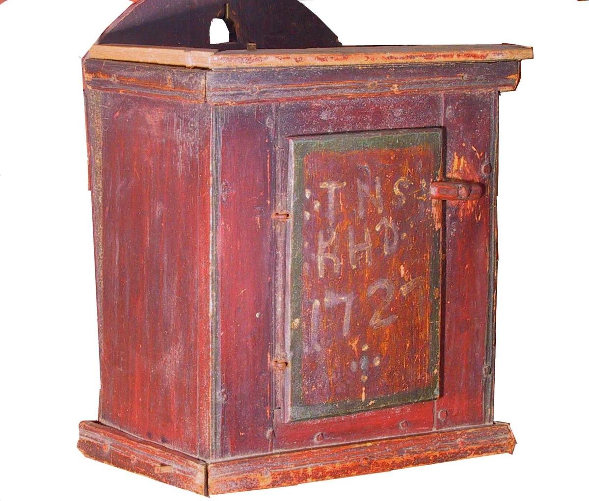 Hengeskap, av furu. Lite, kasseformet rødmalt hengeskap med bakplate med rundet topp hvori hull for krok. Bakplaten eik. Grovt arbeide. En liten dør med slå for i fronten. Skapet har bare ett rom. Gesimslist og forlist. På døren er malt bokstavene TNS & KHD og årstallet 1727.