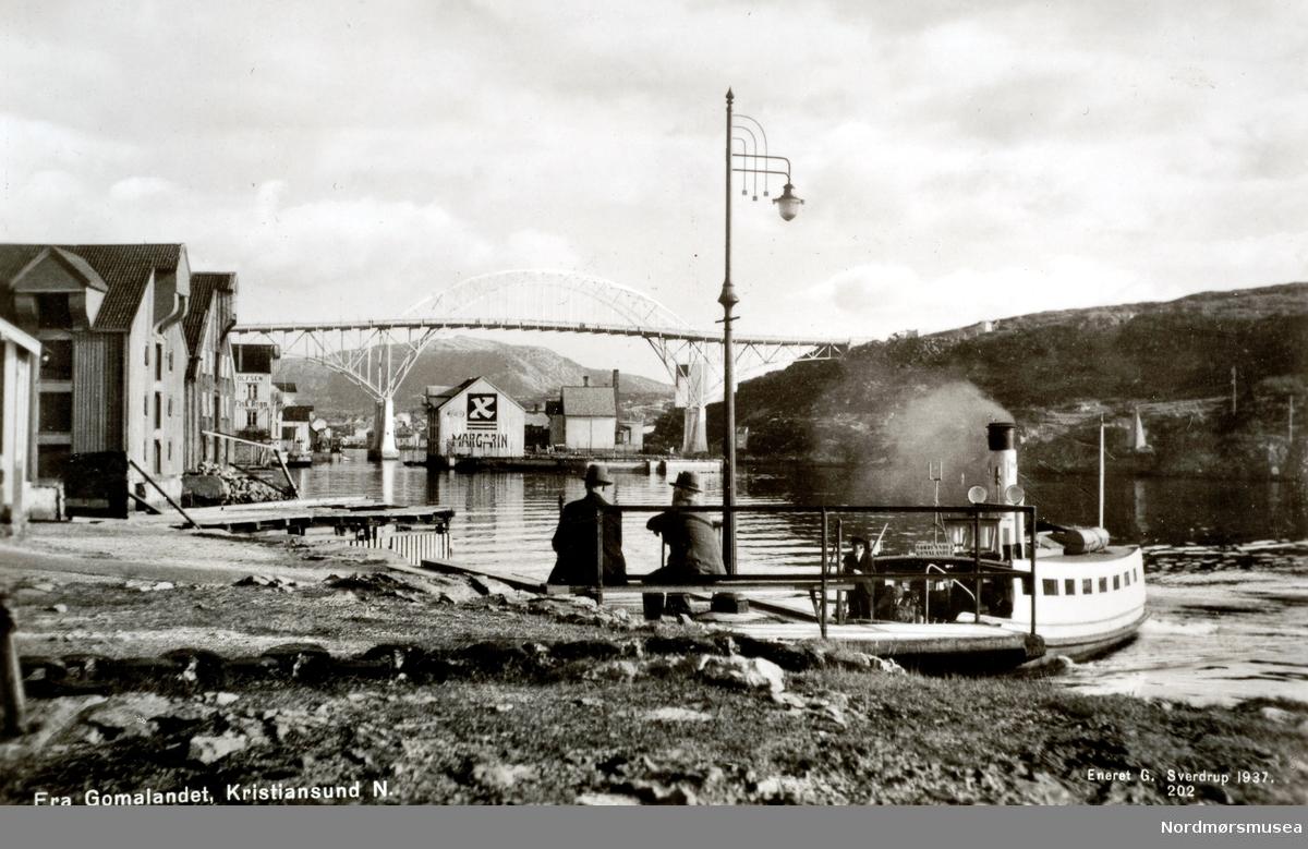 """Sundbåten legger til på Gomalandet i Kristiansund. I bakgrunnen ses Nordholmen under broa og til venstre brygger på Gomalandet. Til høyre ses Nordlandet. Bildet viser sundbåten """"Fram""""som  ble bygget i 1878 ved Trondheims Mekaniske Verksted og var 11,7 meter lang, 2,5 meter bred og hadde en tonnasje på 15,38 bruttotonn. Båten ble senere sertifisert for 45 passasjerer og ble satt i drift 17. juni 1878. Ved utbruddet av andre verdenskrig ble """"Fram"""" senket under bombingen 28. april til 1. mai 1940. Båten ble hevet 8. mai og satt på slipp ved Sterkoder Mek. Verksted, for så å bli reparert der i 1941. Båten opphørte i drift da formannskapet den 21. august 1958 vedtok å overdra """"Fram"""" vederlagsfritt til Havnevesenet som arbeidsbåt.  Kilde for båtene: Sven Erik Olsen og Tor Olsen. Sundbåten. Folk over havna - fra fergemenn til Angvik. Utgitt 2005. (Info: Peter Storvik). --  Postkort med tekst: """";Fra Gomalandet. Kristiansund N.""""; Sundbåten  """"Lyn"""" ligger ved sundbåttillegget på Goma. Bryggene og sentrumsbebyggelsen på Gomalandet sees til venstre langs Nordsundet, og Bjønnahaugen til høyre i bildet. Nordsundbrua går over Nordsundet fra Gomalandet til Nordlandet. Under brua ser vi margarinreklamen på Nordholmen.(Fra Nordmøre Museums fotosamlinger.)"""