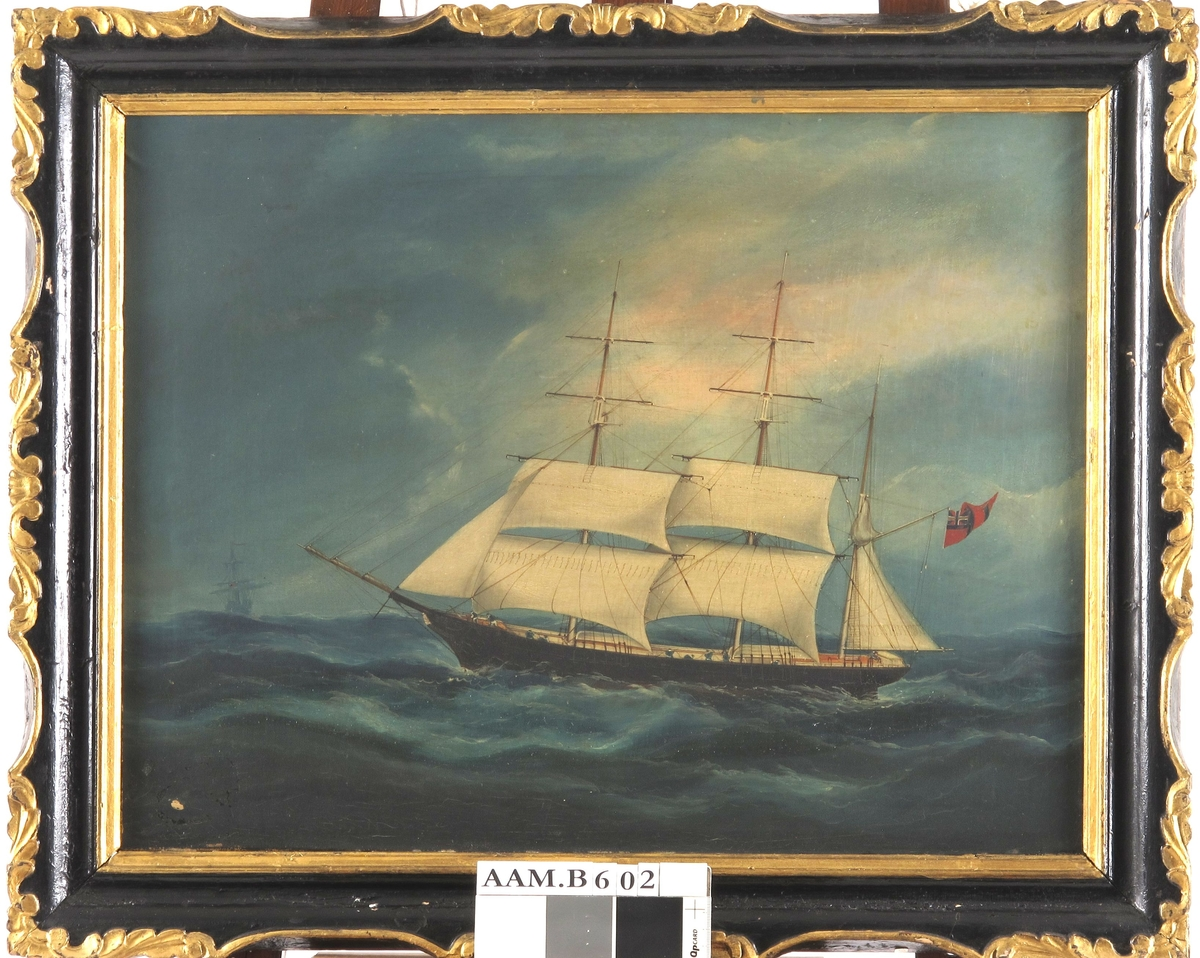 """Bark """"Otilia"""", med kurs mot venstre, redusert seilføring, sortmalt skrog m. navnet malt i baugen, norsk unionsflagg  under gaffelen. Mørk sjø og skyet himmel."""