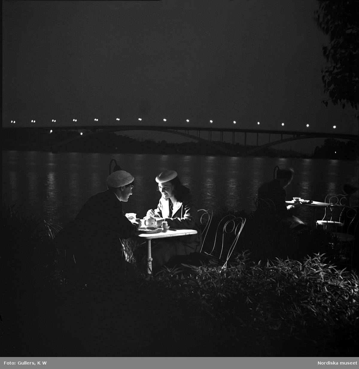 Norr Mälarstrand, Stockholm. Två kvinnor sitter vid ett bord på en uteservering i kvällsbelysning. Riddarfjärden och Västerbron i bakgrunden.