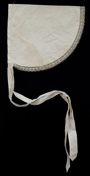 Serveringsforkle i hvit bomull/lin, halv-oval form med knytebånd og kantet med knipling. Ant. hjemmesydd, lerretsvevet stoff.