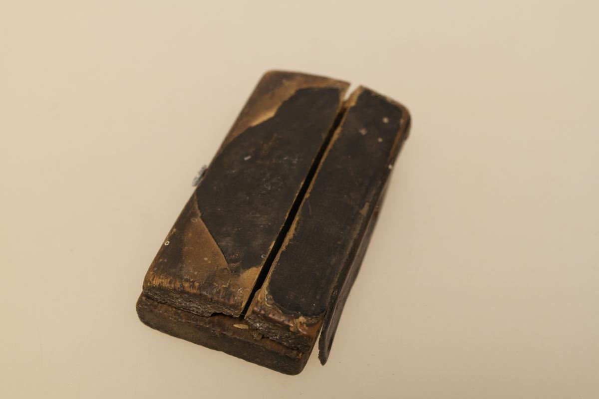 Sneppert (a) med eske (b) til bruk ved årelating.  A) Messingsneppert med jernblad. B) Eske i skåret og pusset furu. Trukket med svart lær utenpå og velour inni. Lukkes med en messinghempe. Skåret initialer i bunnen.