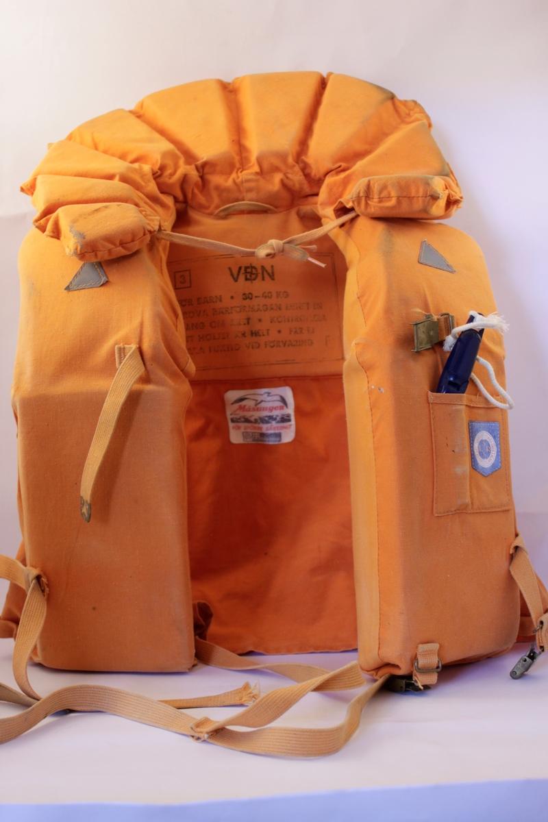 Orange flytväst i bomullstyg med tygremmar och en mörkt blå visselpipa. Flytkrage smat två trekantiga reflexer fram.