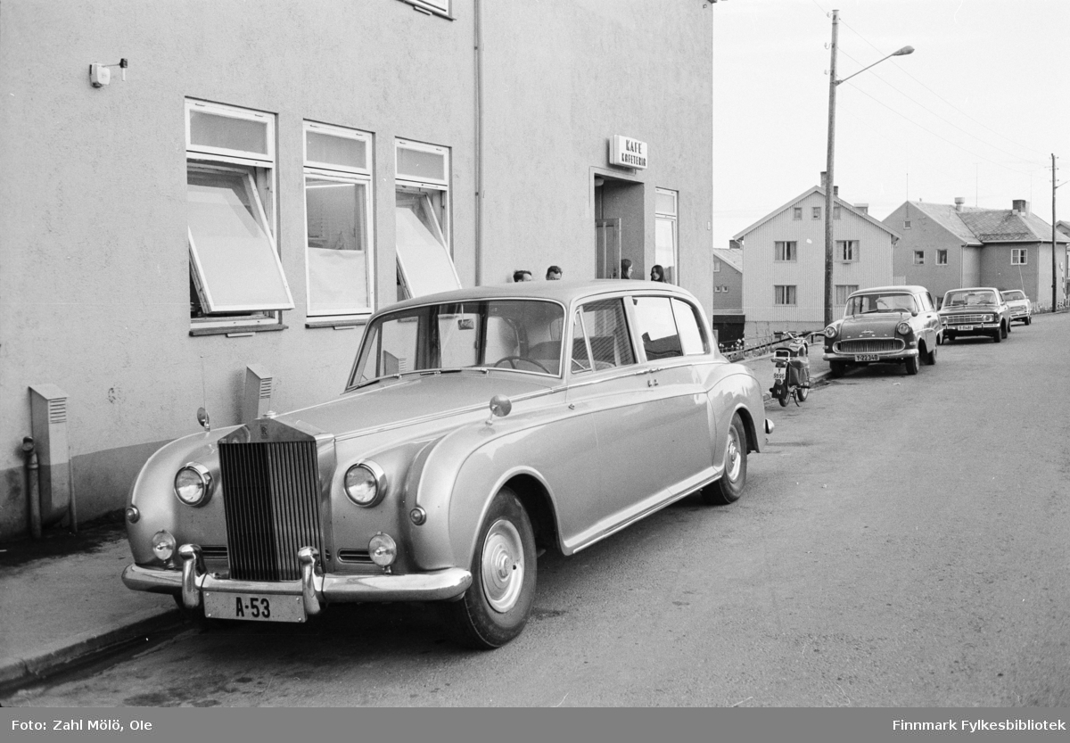 Bildeserie av Ole Zahl Mölö fra 1969 og 1967 av diverse biler.  1967: Rolls Royce (med registerskilt A-53) parkert utenfor kafé i Vadsø. En Opel Rekord Caravan stasjonsvogn 1958-60 (med registerskilt Y-22340) parkert bak Rolls Royce og en motorsykkel. Og bak den står den Ford 17M.